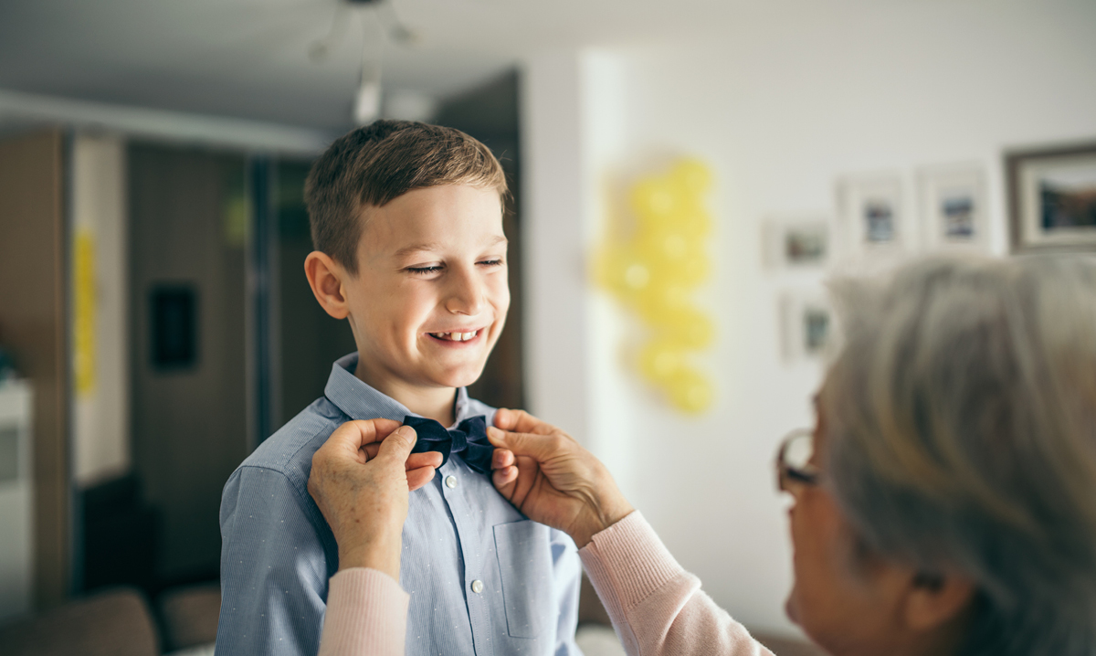Person straightening a young boy's bowtie