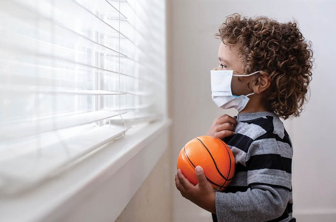 Young child holding a mini basketball and wearing a face mask looks out a window