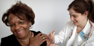elderly woman getting a shot from a doctor