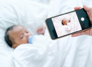 A hand holding a smart phone over a sleeping baby