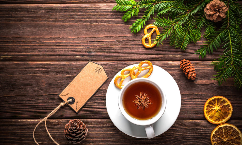 Cup of tea surrounding by winter greenery on a wooden plank table