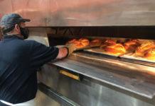 Man at Dakota Break Company checking bread in the oven
