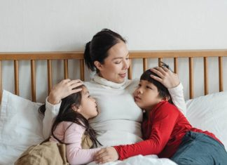 An asian woman hugging two young children who are looking at her while sitting on the couch