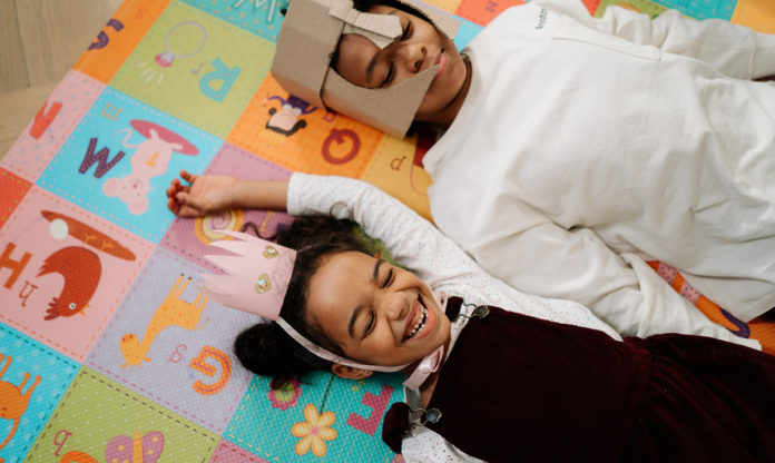 Two young Black kids smiling while wearing costumes and laying on the floor