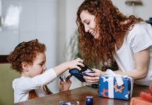 Woman helping a young child unwrap a present