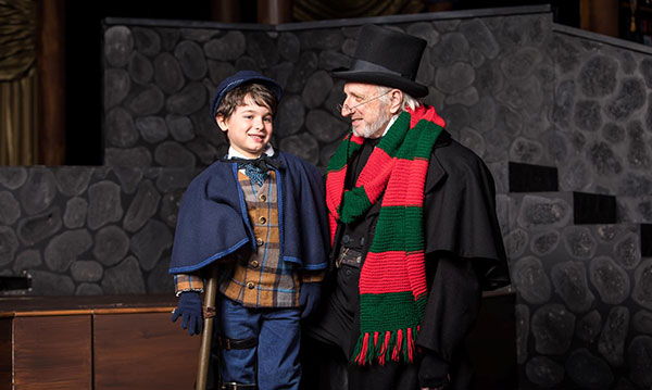 Scrooge and tiny Tim on stage