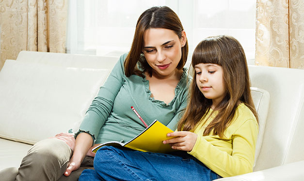 Woman and girl sitting on couch looking at piece of paper