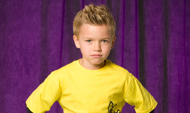Boy with hands on his hips in front of a purple curtain