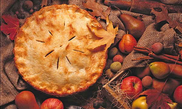 A full apple pie surrounded by apples and leaves on a wood table
