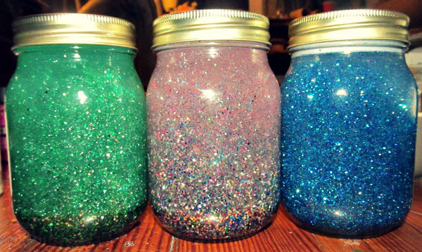 Three jars filled with colorful water and glitter