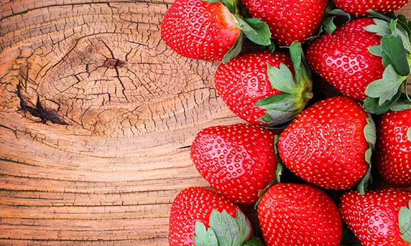 Pile of strawberries on a piece of wood