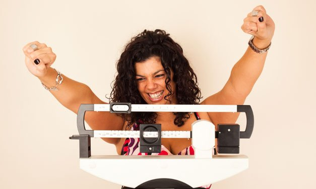 Happy woman on scale with arms in the air