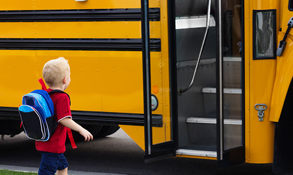 Kindergartner with a red shirt and blue backpack getting on a school bus