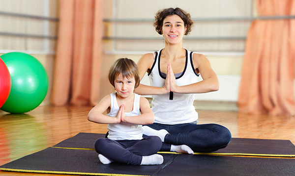 Woman and child in yoga pose at the gym