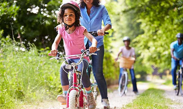 Mom and daughter riding their bikes along a trail