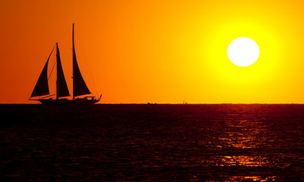 Silhouette of a sailboat against the setting sun
