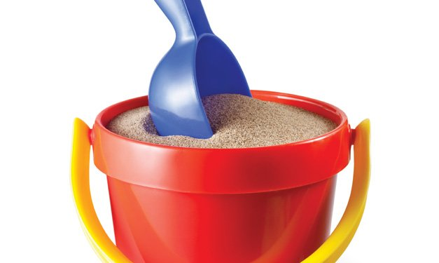 A red bucket full of sand with a purple shovel in it