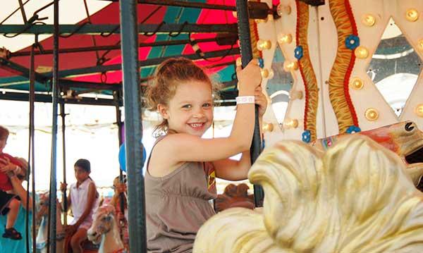 Little girl smiles as she rides a carousel