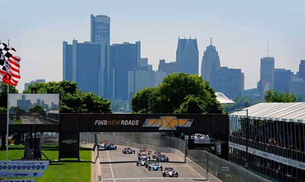 Cars racing on Belle Isle with the Detroit skyline in the background
