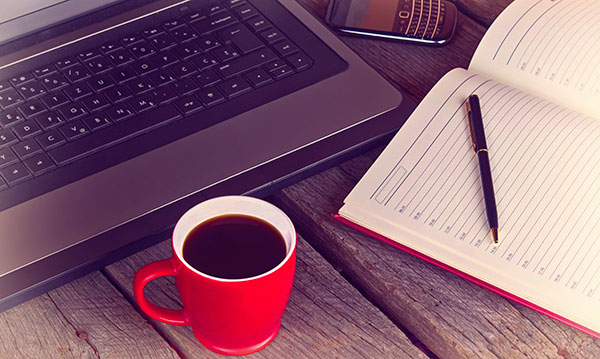 Cup of coffee, a laptop and a notebook and pen on a wood table