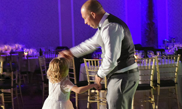Man and little girl dancing together