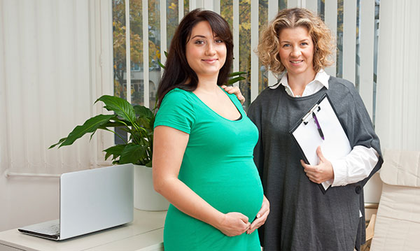 Pregnant woman in green standing next to woman in grey holding a clipboard