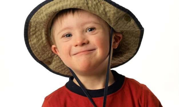 A young boy who has down syndrome smiles while wearing a hat
