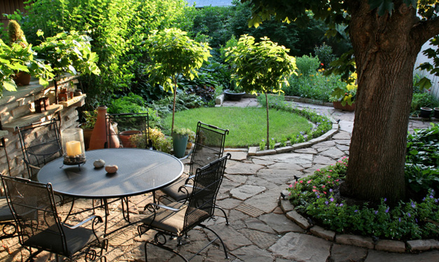 Tree-filled backyard with a patio set and stone pavers