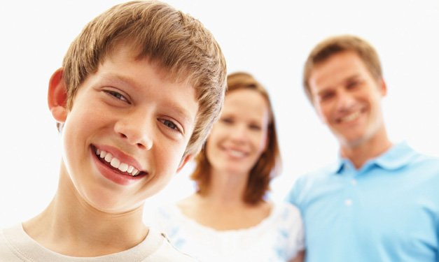 Close-up of smiling boy with woman and man in the background