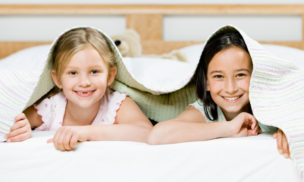 Two girls smiling from under a blanket
