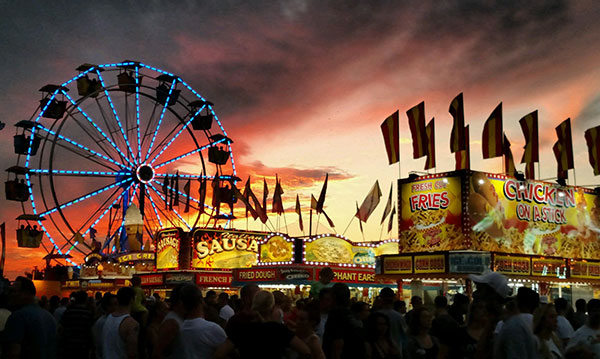 Silhouettes of a carnival on a pink and grey sky