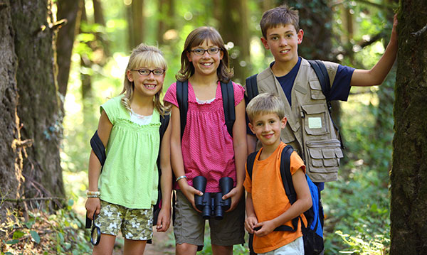 Four kids hiking through the woods