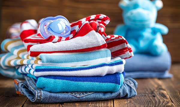 Stack of kids clothes with a pacifier on top