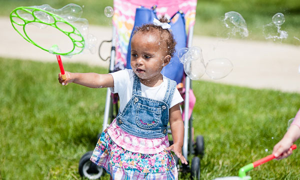 Toddler in front of stroller playing with bubbles