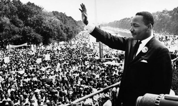 Black and white photo of Dr. Martin Luther King Jr. waving at a crowd