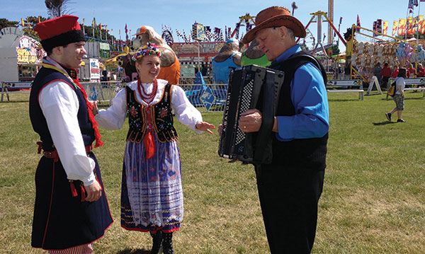 Three Polish dancers and musicians at a fair