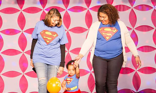 Two women and a little girl in Superman shirts walk the runway