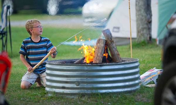 Boy sitting next to a campfire