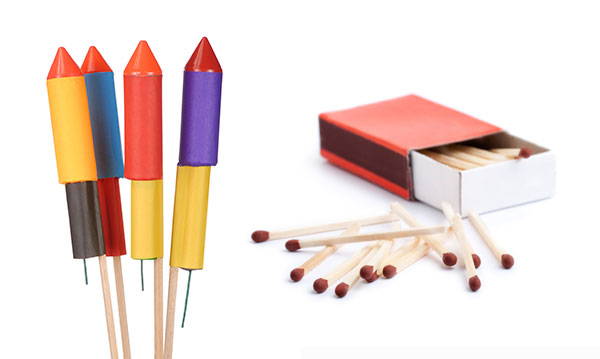 Four Roman candles and a box of matches on a white background