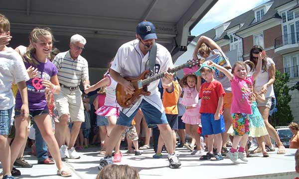 Man plays guitar as kids dance at a music in the park event