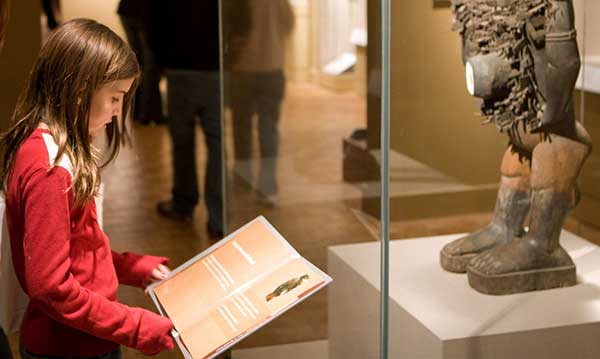 Girl reads the description of an artifact at a musem