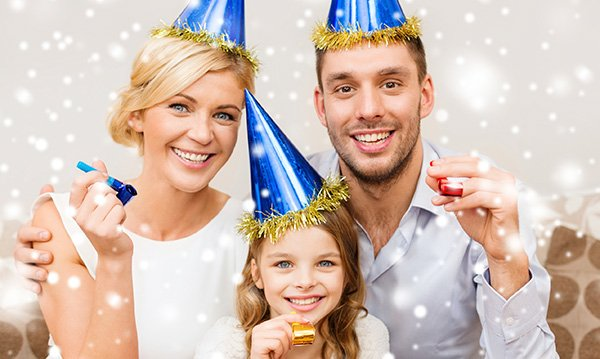 Woman, man and child in blue and gold party hats with noisemakers surrounded by white orbs