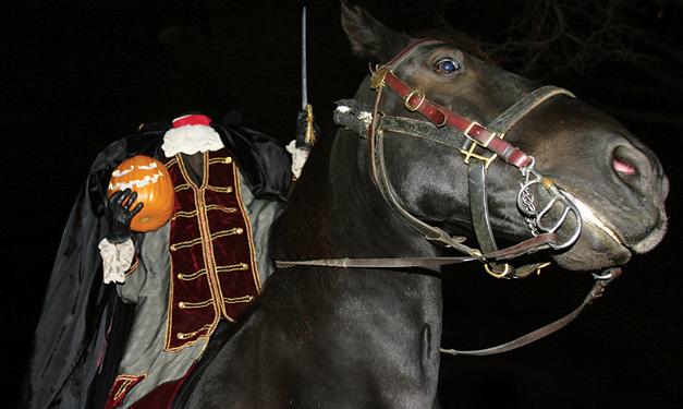 Headless man holding a pumpkin head on a black horse