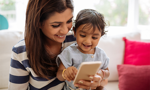 A mom and her child playing with a smartphone