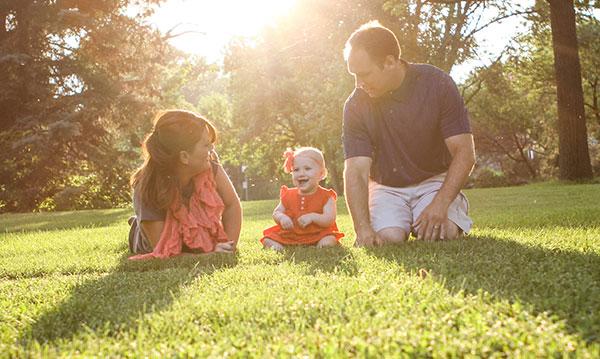 Family of three sitting in a park on a sunny day