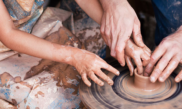 Child hands and adult hands making a pot on a pottery wheel