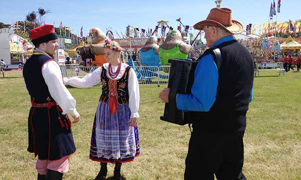 Three people in traditional polish clothing in front of the rides at St. Mary's Polish Country Fair