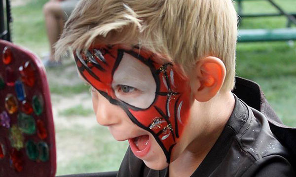 Little boy showing off spiderman face paint