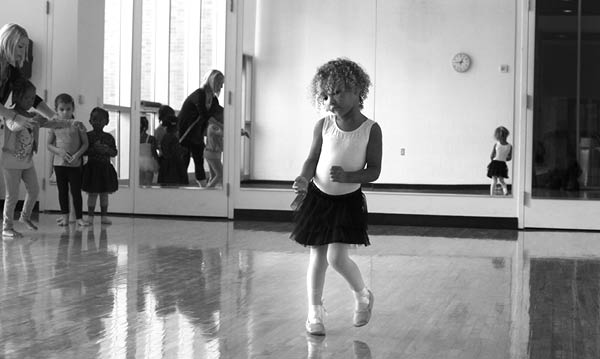 Black and white image of a little girl dancing in a dance studio