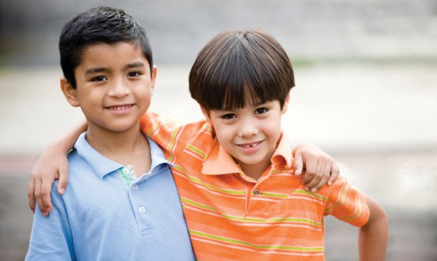 Two boys smiling and side-hugging one another